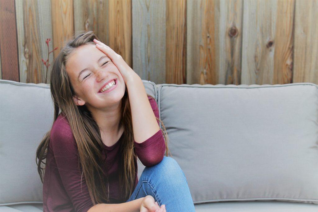 Leende jente som sitter i en grå sofa