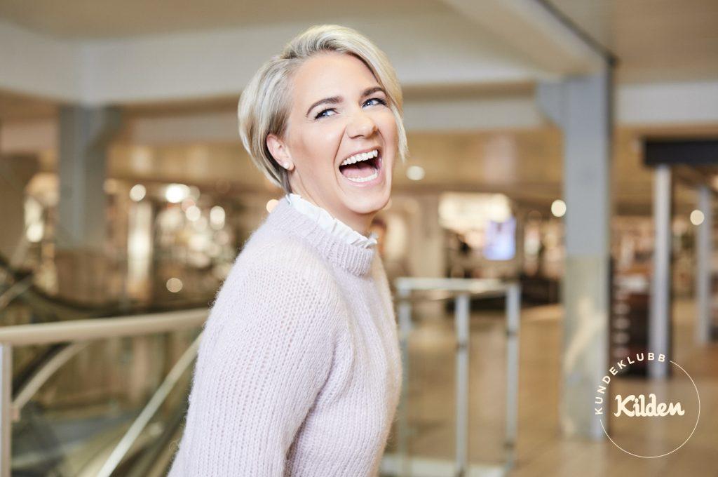 Sprudlende glad kvinne med masse utstråling står i 2.etasje på Kilden Senter